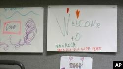 """Gambaran anak-anak dengan tulisan yang berbunyi """"Selamat datang di Amerika, Amerika adalah tempat yang baik,"""" diperagakan hari Senin, 24 April 20017 di Jewish Family Service Refugee and Immigrant Service Center di kota Kent, Washington (foto: AP Photo/Ted S. Warren)"""