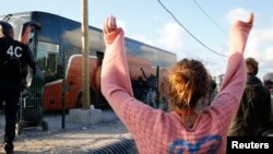 """A volunteer waves to migrant minors in a bus during their transfer by French authorities to reception centers across the country at the end of the dismantlement of the camp called """"the Jungle"""" in Calais, France, Nov. 2, 2016."""