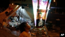 A boy stands near a traditional lantern, marking the Islamic month of Ramadan, with a poster of Egypt's ousted President Mohammed Morsi in a park in front of Cairo University, July 16, 2013.