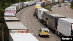 A police vehicle drives past trucks backed up on the M20 motorway which leads from London to the Channel Tunnel terminal at Ashford and the Ferry Terminal at Dover, June 23, 2015.