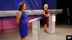 U.S. Rep. Martha McSally, R-Ariz., left, and U.S. Rep. Kyrsten Sinema, D-Ariz., prepare their remarks in a television studio prior to a televised debate, Oct. 15, 2018, in Phoenix. They're running for the U.S. Senate seat being vacated by Republican Jeff