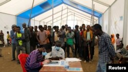 Les Éthiopiens fuyant la région du Tigré s'inscrivent comme réfugiés au camp de transit de Hamdeyat, qui abrite des réfugiés fuyant les combats dans la région du Tigré, à la frontière du Soudan, le 1er décembre 2020.