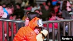 一名中国妇女带着小孩在春运时期的火车站等待上车 (资料图片)