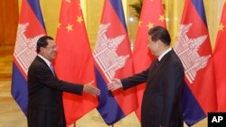 Cambodian Prime Minister Hun Sen, left, shakes hands with China's President Xi Jinping before a meeting at the Great Hall of the People in Beijing Friday, Nov. 7, 2014. (AP Photo/Jason Lee, Pool)