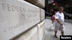 People walk past the Federal Reserve building where talks were held by officials regarding the situation with investment bank Lehman Brothers in New York, September 14, 2008. Talks faltered when Britain's Barclays Plc, which had appeared to be front-runne