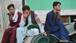 Afghan men sit in a courtyard inside a Shiite mosque in Kandahar on Oct. 15, 2021, after a suicide bomb attack during Friday prayers that killed more than 30 people.