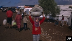A Syrian girl who fled with her family from the violence in their village, carries a plastic container over her head as she walks to fill it with water at a displaced camp, in the Syrian village of Atma, near the Turkish border with Syria, November 10, 20