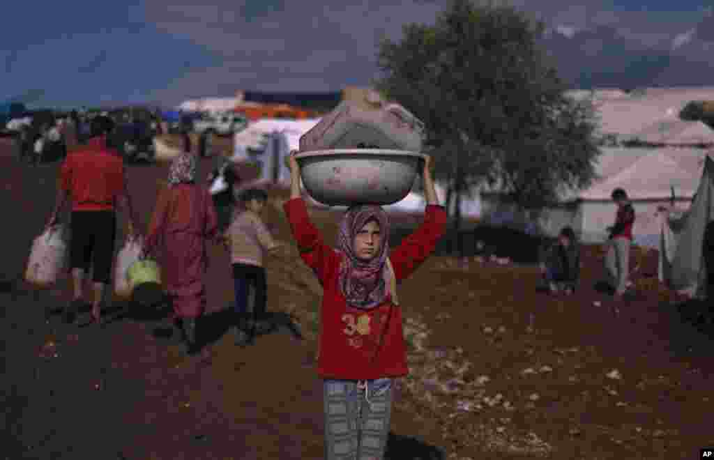 A Syrian girl who fled with her family carries a plastic container over her head as she walks to fill it with water at a displaced camp in the Syrian village Atma, near the Turkish border with Syria, November 10, 2012.