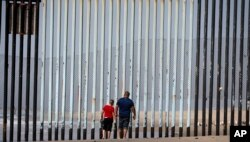 FILE - Two people walk towards metal bars marking the United States border where it meets the Pacific Ocean, in Tijuana, Mexico, March 2, 2016.