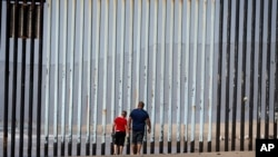 Two people walk towards metal bars marking the United States border where it meets the Pacific Ocean, March 2, 2016, in Tijuana, Mexico. Mexico's President Enrique Pena Nieto has said his country does not intend to pay.