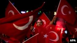 (资料图)土耳其政府支持者们在伊斯坦布尔塔克西姆广场挥舞土耳其国旗并高喊口号。