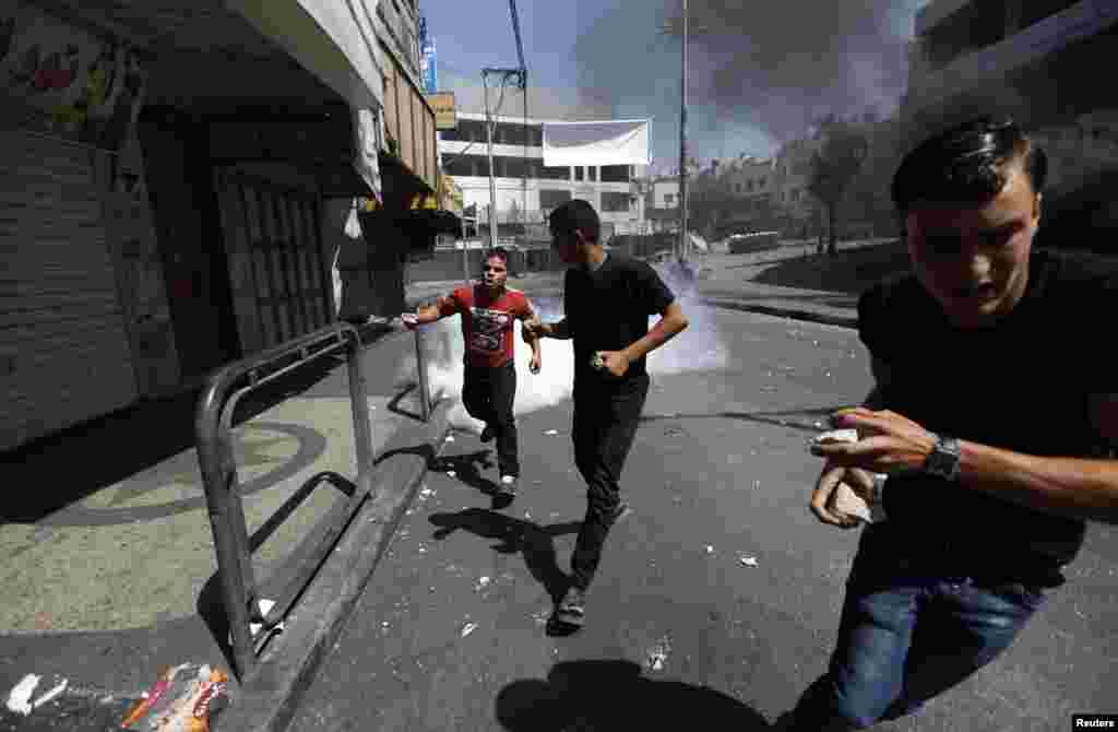 Protesters run from tear gas fired by Palestinian riot police in Hebron, Aug. 22, 2014.