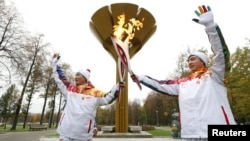 Student Anatoly Chentuloev (R) and journalist Yeon Kyu-sun pose for a picture during the the Sochi 2014 Winter Olympic torch relay in Moscow Oct. 8, 2013.