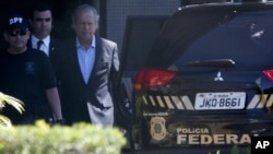 FILE - Jose Dirceu, former presidential chief of staff, center, is accompanied by federal police agents to a car at a police station in Brasilia, Aug. 4, 2015.