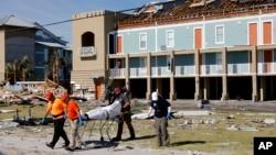 Petugas mengevakuasi jenazah yang ditemukan dalam pencarian di sebuah puing bangunan setelah Badai Michael melanda di Pantai Mexico, Florida, 12 Oktober 2018.