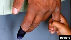 Seorang anak memegang tangan ayahnya yang telah memberikan suara di sebuah TPS di Kabul (14/6).