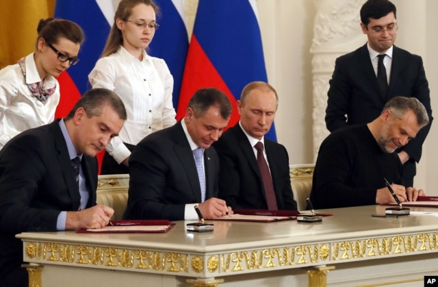 Russian President Vladimir Putin (2nd R) looks on as the Speaker of Crimean legislature Vladimir Konstantinov (2nd L), Crimean Premier Sergei Aksyonov (L), and Sevastopol mayor Alexei Chalyi, (R), sign a treaty for Crimea to join Russia, Moscow, March 18, 2014.