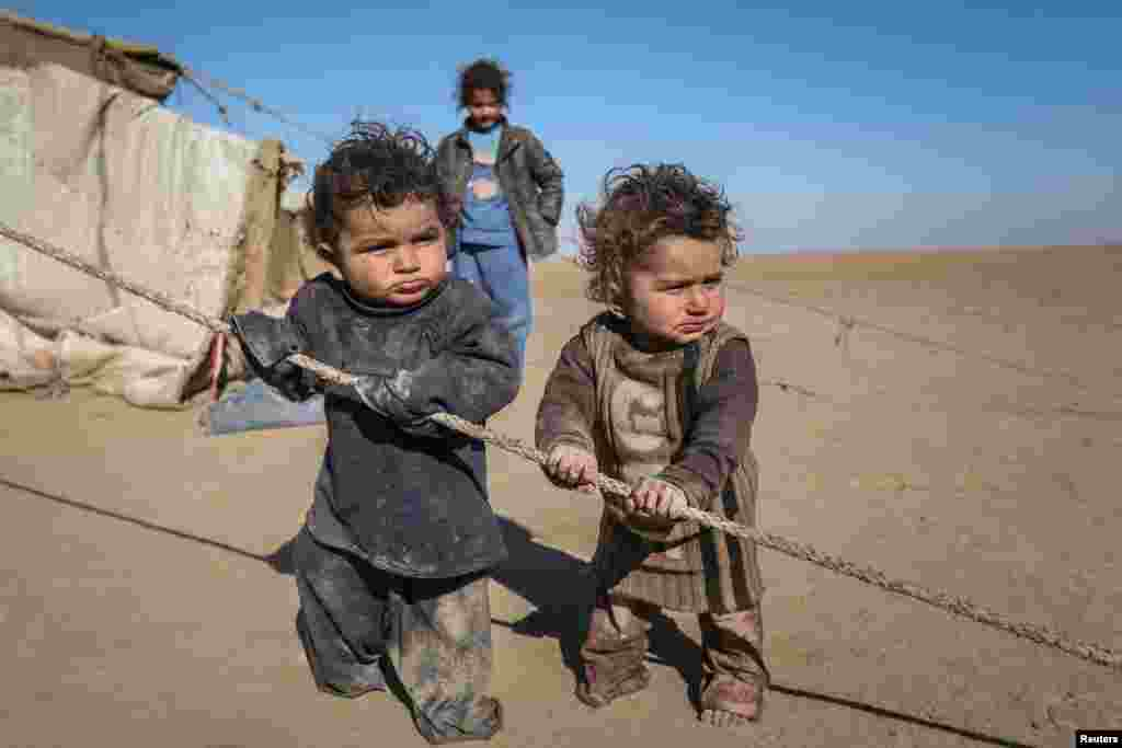 Internally displaced Syrian children who fled Raqqa city stand near their tent in Ras al-Ain province, Syria, Jan. 22, 2017.