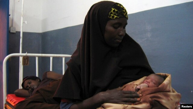 A Somali woman holds a newborn baby at a hospital run by Doctors Without Borders, Jowhar, north of Mogadishu, Aug. 3, 2007.