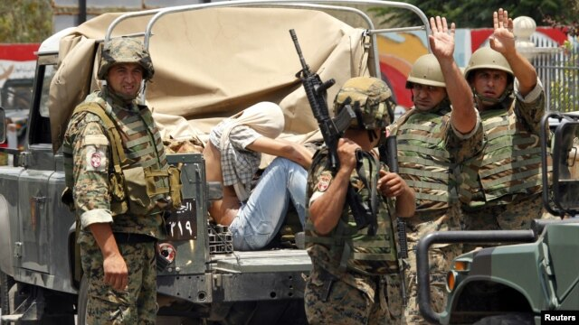 Lebanese army soldiers gesture as they capture a gunman in Sidon, southern Lebanon, June 24, 2013.