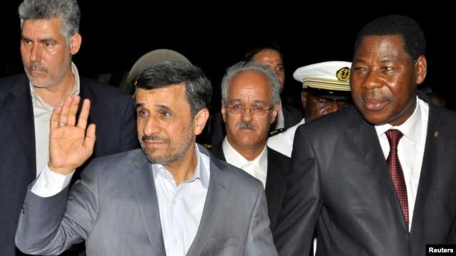 Iranian President Mahmoud Ahmadinejad (2nd L) waves next to Benin's President Thomas Boni Yayi (R) as he arrives in Cotonou April 14, 2013.