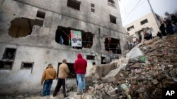 Palestinians gather by a destroyed house of Raeb Ahmed Muhammad Alivi that was demolished by the Israeli army in the West Bank city of Nablus, Thursday, Dec. 3, 2015.