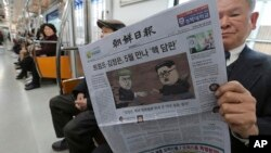 A passenger reads a newspaper with headline of a planned summit meeting between North Korean leader Kim Jong Un and U.S. President Donald Trump, left, at subway train in Seoul, South Korea, March 10, 2018.