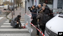 Watched by the media a woman lays a flower tribute at the site of the attack on a kosher market in Paris, France, Saturday, Jan. 10, 2015. (AP Photo/Laurent Cipriani)