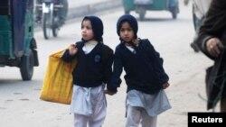 Dua anak perempuan berjalan bergandengan sambil menenteng tas mereka menuju sekolah di Peshawar (12/1).