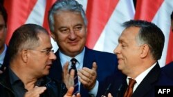 Hungarian PM Viktor Orban (R) celebrates with his party leader of their governing FIDESZ party, vice-president Lajos Kosa (L) and deputy prime minister Zsolt Semjén of the Christian Democratic People's Party in Budapest, Oct. 2, 2016.