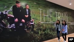 """In this March 15, 2018, photo, two women walk past a mural of a Paul Fusco photograph that is part of the exhibit, """"The Train: RFK's Last Journey,"""" at the San Francisco Museum of Modern Art in San Francisco."""