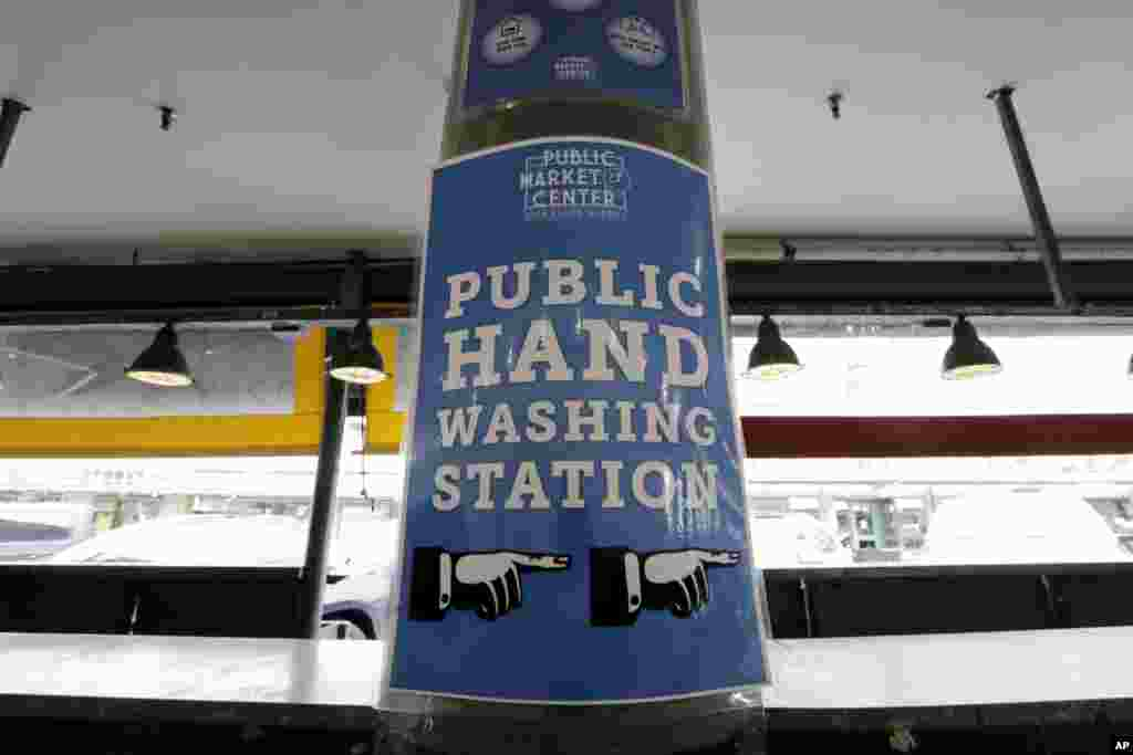 A sign directs visitors to a nearby hand washing station in front of empty vendor booths at the Pike Place Market, March 17, 2020, in Seattle, Washington.