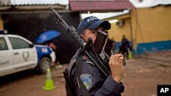 A member of the Honduran National Police outside a police station near El Mayoreo markert in Tegucigalpa, Honduras, June 1, 2013.