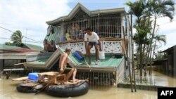 Cư dân sử dụng một chiếc bè tự chế để di chuyển tại thị trấn Calumpit, tỉnh Bulacan, Philippines, ngày 3/10/2011