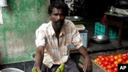 A man sells eggplant in an Indian market.