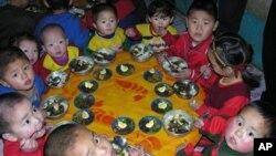 ໃນຮູບນີ້ ຈາກອົງການອາຫານໂລກ ຫລື World Food Program, ເດັກນ້ອຍ ເກົາຫລີເໜືອ ກໍາລັງກິນເຂົ້າ ທ່ຽງ ຊຶ່ງມີໂຮມທັງເຂົ້າ ທີ່ໄດ້ຮັບການຊ່ວຍເຫລືອ ຈາກອົງການອາຫານໂລກ ຢູ່ສະຖານທີ່ລ້ຽງເດັກ ແຫ່ງນຶ່ງ ໃນເກົາຫລີເໜືອ.