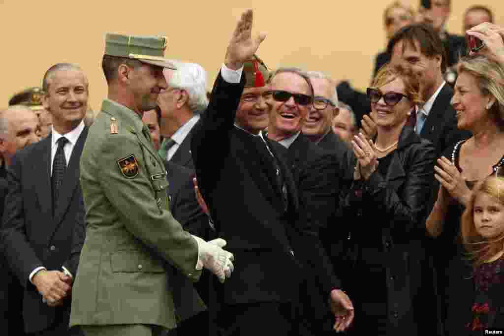 """Nam tài tử kiêm đạo diễn điện ảnh người Tây Ban Nha Antonia Banderas vẫy tay chào đám đông sau khi được phong chức Lính viễn chinh Danh dự Tây Ban Nha với chiếc mũ """"chapri"""" trong buổi lễ ở Malaga, miền nam Tây Ban Nha. Bà vợ ông, diễn viên điện ảnh Mỹ Malanie Griffith (hàng thứ hai bên phải) vỗ tay."""