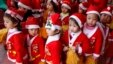 FILE - Children dressed in Santa Claus outfits line up before a Christmas celebration at a kindergarten in Hanoi.