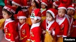 Trẻ em trong trang phục ông già Noel xếp hàng tại một trường mầm non ở Hà Nội.