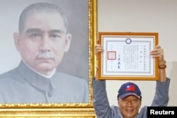 Terry Gou, founder of Foxconn, holds a testimonial next to a portrait of Sun Yat-sen, the founding father of Taiwan, as he announces his bid for the nomination of the opposition Kuomintang party to run for the island's presidency, in Taipei, Taiwan, April 17,2019.