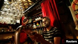 Bartender Samet Kardas smokes as he serves beer at a bar in Istanbul, Turkey, Jul. 14, 2009.