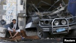 Seorang anak laki-laki Yaman duduk di samping mobil yang terkena serangan udara koalisi pimpinan Saudi di provinsi Amran (29/8).