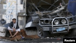 A boy sits next to a car destroyed by a Saudi-led air strike in Yemen's northwestern province of Amran, Aug. 29, 2015. (REUTERS/Khaled Abdullah)