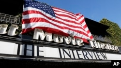 """""""The Interview,"""" the comedy starring Seth Rogen and James Franco, is listed under an American flag on the marquee of the Cinefamily at Silent Movie Theater in Los Angeles, Dec. 25, 2014."""