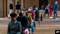 Des policiers sont assis sur les chaises pendant qu'ils font la queue pour être contrôlés et testés pour COVID-19 à Johannesburg, Afrique du Sud, le jeudi 7 mai 2020. (AP Photo/Themba Hadebe)