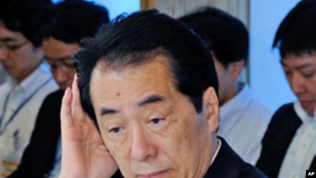 Japanese Prime Minister Naoto Kan gestures upon his arrival for a cabinet meeting on environment and energy at Kan's official residence in Tokyo, June 22, 2011