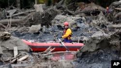 Nhân viên cứu hộ sử dụng một chiếc thuyền nhỏ để len qua những mảnh vỡ trong vụ sạt lở đất kinh hoàng ở thị trấn Oso, bang Washington.