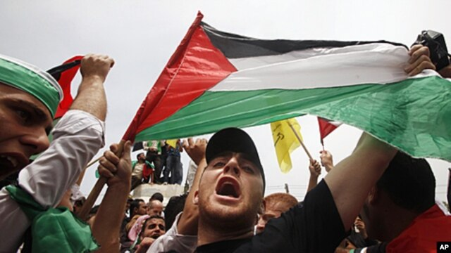 A Palestinian holds up a flag as he celebrates the reconciliation agreement between rival Palestinian factions Fatah and Hamas during a rally in Gaza City, May 4, 2011
