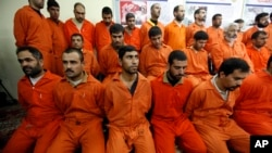 FILE - Handcuffed al-Qaida linked suspects sit in the terrorist combat and organized crime department in Baghdad, Iraq, Dec. 2, 2010.