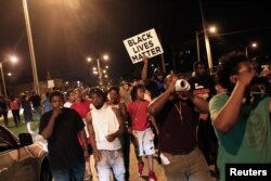 Protesters march during disturbances following the police shooting of a man in Milwaukee, Wisconsin, Aug. 14, 2016.